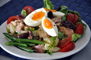a plate of salade nicoise , tuna, ripe red tomatoes, lightly cooked green beans, potato salad, olives  and soft boiled egg