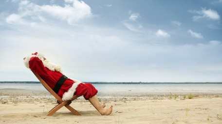 Barefoot Santa relaxing in a deck chair on the beach